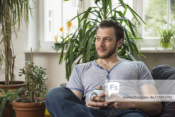 Thoughtful mid adult man drinking coffee in living room and thinking  Munich  Bavaria  Germany