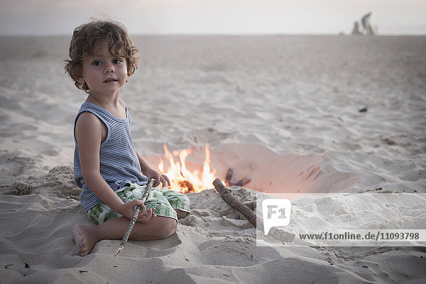 Boy sitting next to camp fire on beach and family in the background