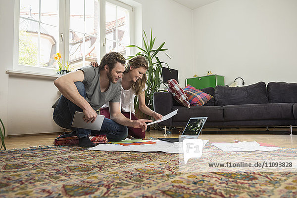 Couple looking at map in living room  Munich  Bavaria  Germany