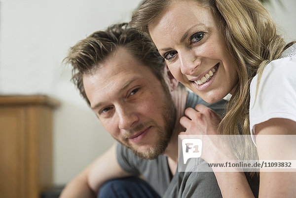 Portrait of couple in living room and smiling  Munich  Bavaria  Germany