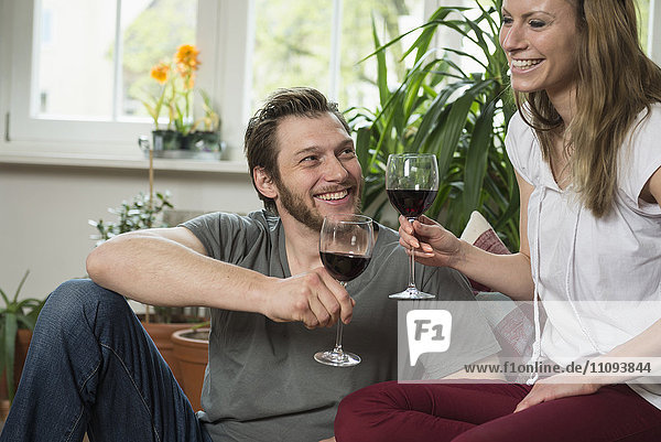 Couple drinking red wine in living room and smiling  Munich  Bavaria  Germany