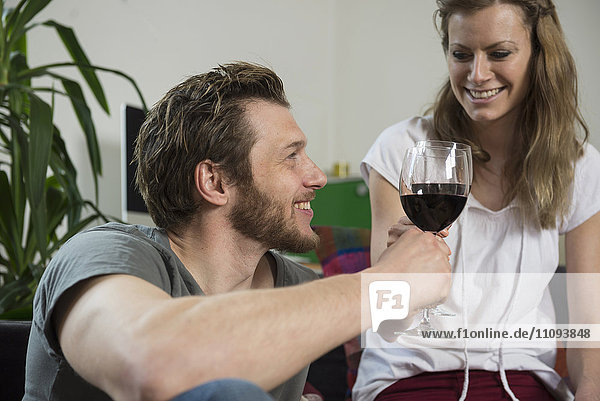 Couple drinking red wine in living room and smiling  Munich  Bavaria  Germany Couple drinking red wine in living room and smiling, Munich, Bavaria, Germany
