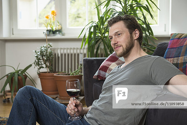 Thoughtful mid adult man drinking red wine in living room  Munich  Bavaria  Germany