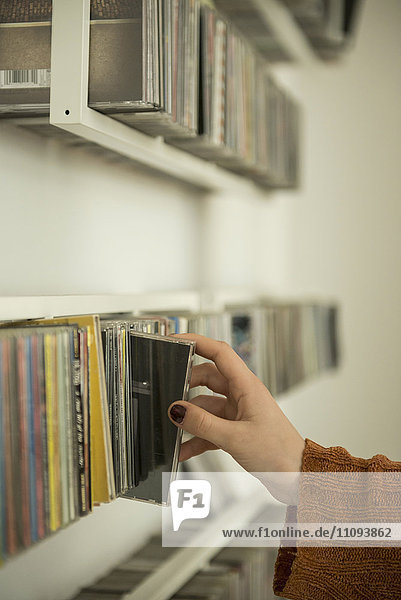 Close-up of a woman hand picking a cd from shelf  Munich  Bavaria  Germany