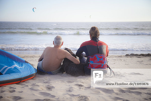 Rear view of kite surfer with his father sitting on the beach