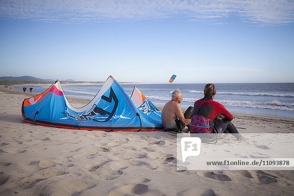 Kite surfer with his father sitting on the beach