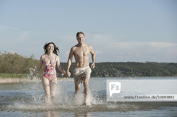 Mature couple running through the water in lake  Bavaria  Germany