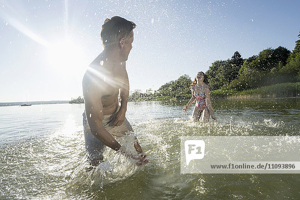 Mature couple splashing water to each other on lake  Bavaria  Germany