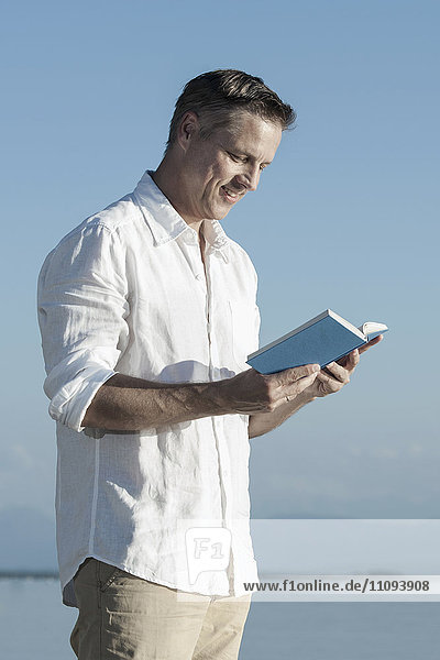 Mature man reading book and smiling at lakeside  Bavaria  Germany