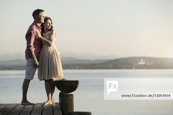 Mature couple standing on pier and looking over lake  Bavaria  Germany Mature couple standing on pier and looking over lake, Bavaria, Germany