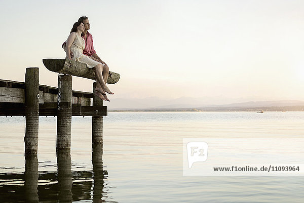 Mature couple sitting on pier looking over lake  Bavaria  Germany