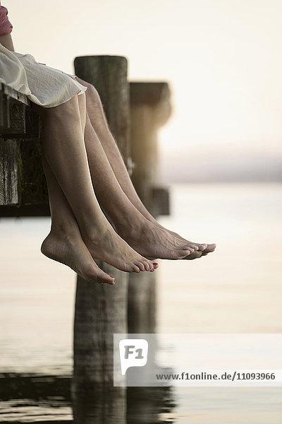 Couple legs dangling on pier  Bavaria  Germany
