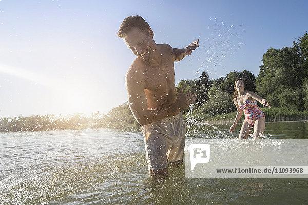 Mature woman splashing water on her husband on lake  Bavaria  Germany