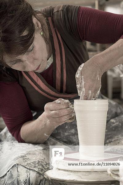 Female potter moulding clay in workshop  Bavaria  Germany Female potter moulding clay in workshop, Bavaria, Germany