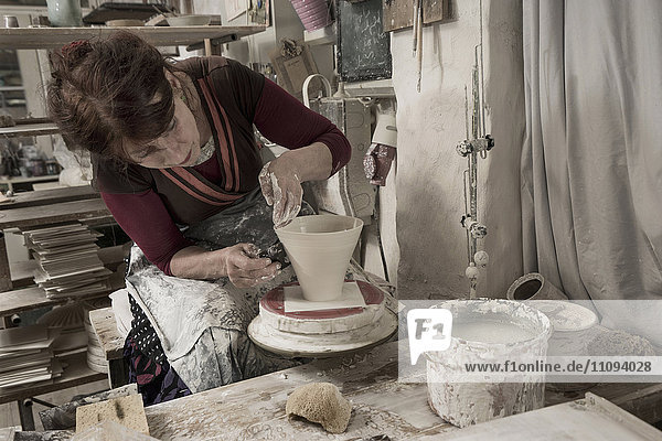 Female potter moulding clay in workshop  Bavaria  Germany
