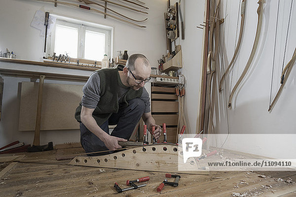 Male bow maker fixing wood in bow shape in workshop  Bavaria  Germany