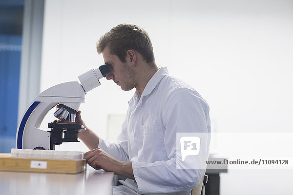 Young male scientist looking through microscope in lecture room