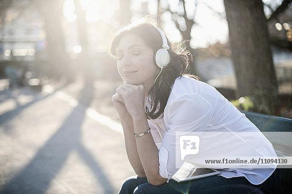 Mature woman listening to music and sitting in the park bench  Bavaria  Germany Mature woman listening to music and sitting in the park bench, Bavaria, Germany