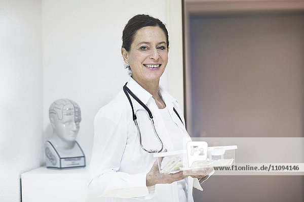 Portrait of a female doctor holding a medicine box