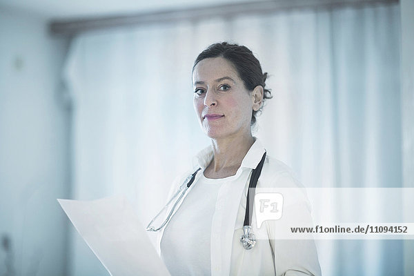 Portrait of a confident female doctor holding a medical report