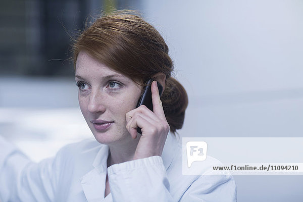 Young female engineer talking on a mobile phone near switchgear in an industrial plant