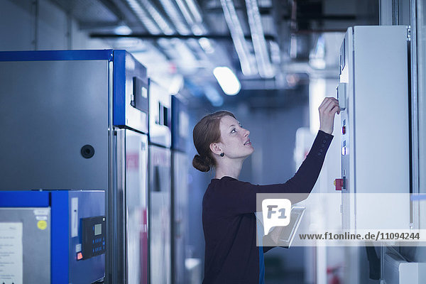 Young female engineer controlling a switchgear in control room