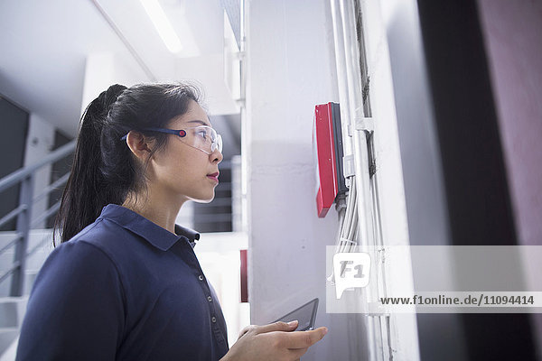 Young female engineer updating control panel using digital tablet in an industrial plant