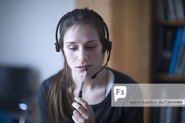 Young woman wearing headset and thinking