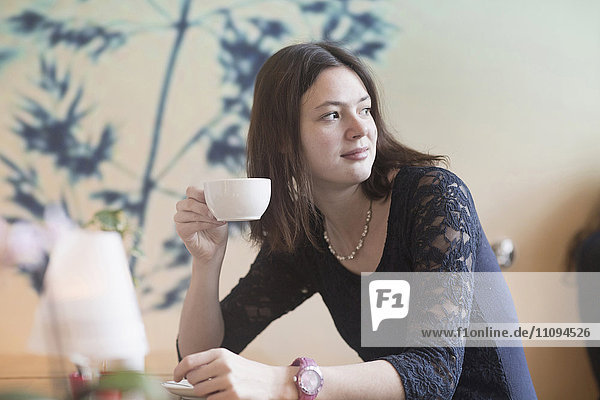 Young woman drinking coffee in coffee shop