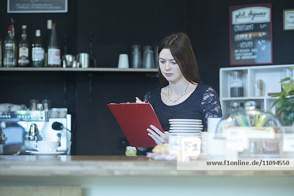 Young woman checking checklist in coffee shop