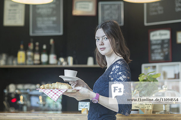 Young waitress serving coffee and croissant in coffee shop