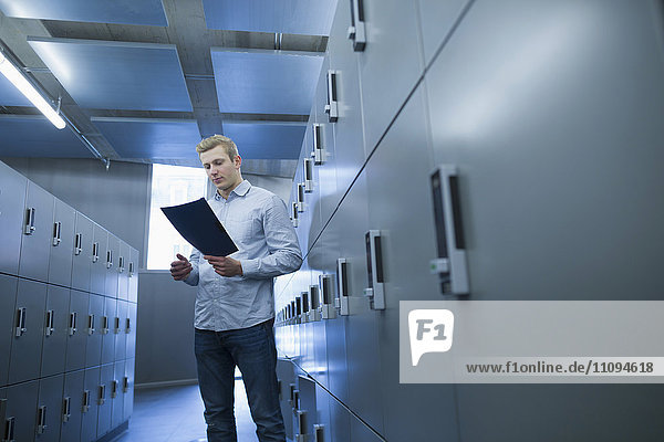 Young university student reading document file in locker room