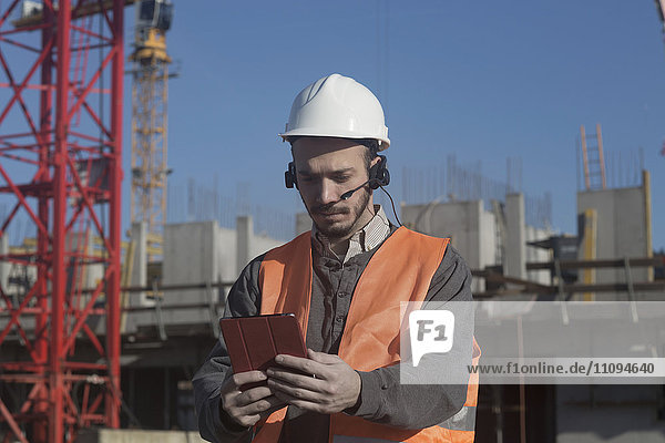 Young male engineer using digital tablet at construction site