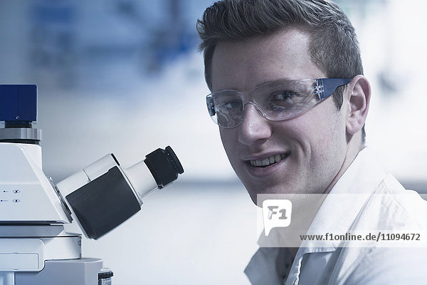 Portrait of a young male scientist using microscope in an optical laboratory