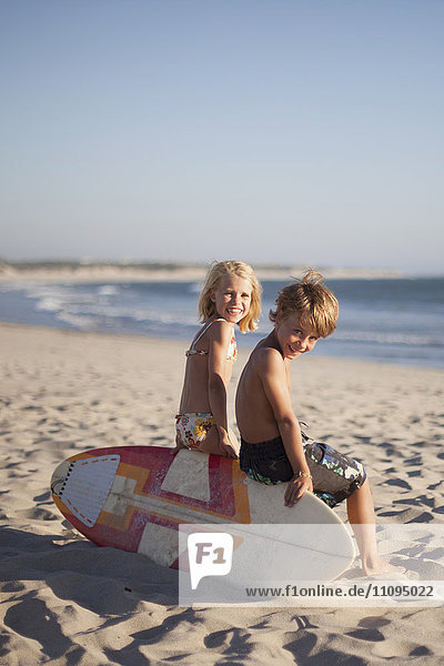 Two children sitting on bodyboard at the beach  Viana do Castelo  Norte Region  Portugal