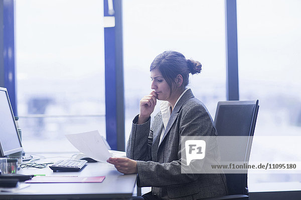 Businesswoman reviewing paperwork at desk in office  Freiburg Im Breisgau  Baden-Württemberg  Germany