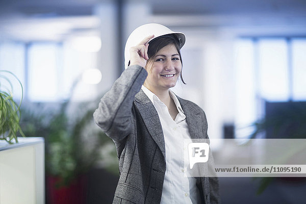 Portrait of a businesswoman smiling in an office and wearing hardhat  Freiburg Im Breisgau  Baden-Württemberg  Germany