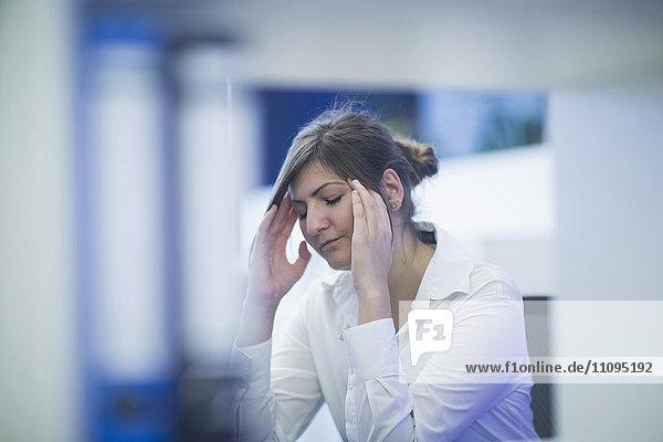 Businesswoman suffering from a headache in an office  Freiburg Im Breisgau  Baden-Württemberg  Germany