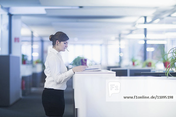 Businesswoman standing and reading document in cubicle  Freiburg Im Breisgau  Baden-Württemberg  Germany