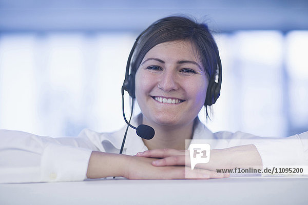 Happy businesswoman wearing headset in office  Freiburg Im Breisgau  Baden-Württemberg  Germany