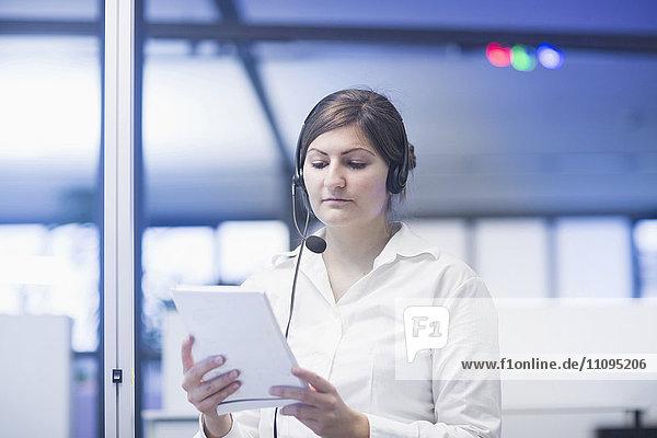 Businesswoman wearing headset and reading document  Freiburg Im Breisgau  Baden-Württemberg  Germany