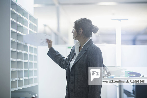 Businesswoman sorting papers in filing cabinet  Freiburg Im Breisgau  Baden-Württemberg  Germany