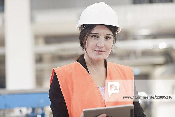 Female engineer using a digital tablet in an industrial plant  Freiburg Im Breisgau  Baden-Württemberg  Germany