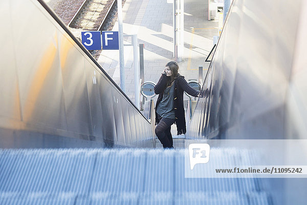 Young woman moving on escalator and talking on phone at railway station  Freiburg im Breisgau  Baden-Württemberg  Germany