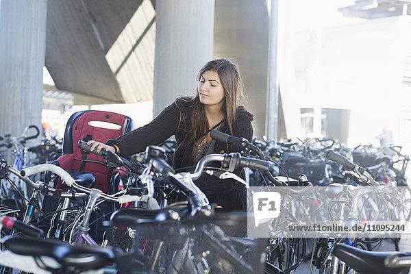 Young woman parking her bicycle  Freiburg im Breisgau  Baden-Württemberg  Germany