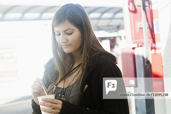 Young woman drinking coffee in city  Freiburg im Breisgau  Baden-Württemberg  Germany