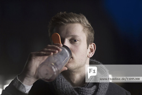 Young businessman drinking energy drink and working till late night  Freiburg im Breisgau  Baden-Württemberg  Germany