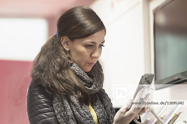 Young woman buying smart phone in the mobile shop,  Freiburg im Breisgau,  Baden-Württemberg,  Germany