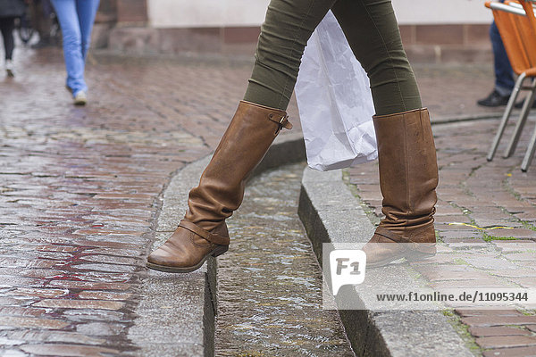 Low section of a woman crossing over drain with shopping bag,  Freiburg im Breisgau,  Baden-Württemberg,  Germany