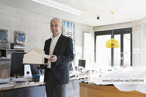 Portrait of a senior architect showing architectural model and standing in the office  Freiburg im Breisgau  Baden-Württemberg  Germany